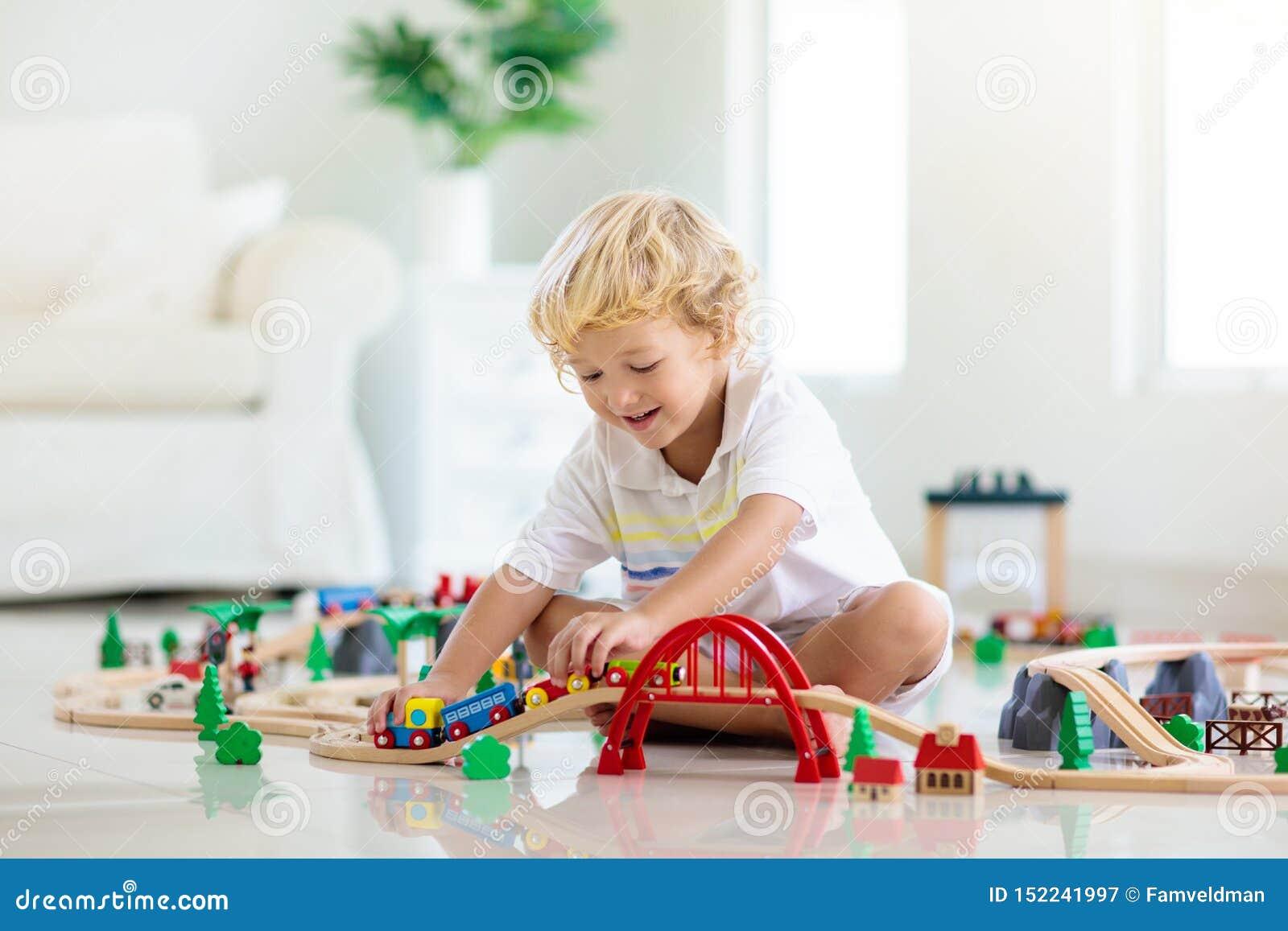 Дети играют деревянную железную дорогу Ребенок с поездом игрушки