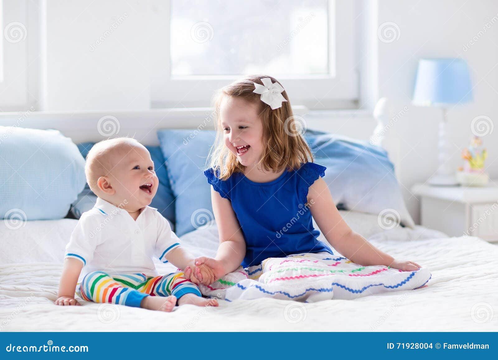 Дети играя на кровати родителей