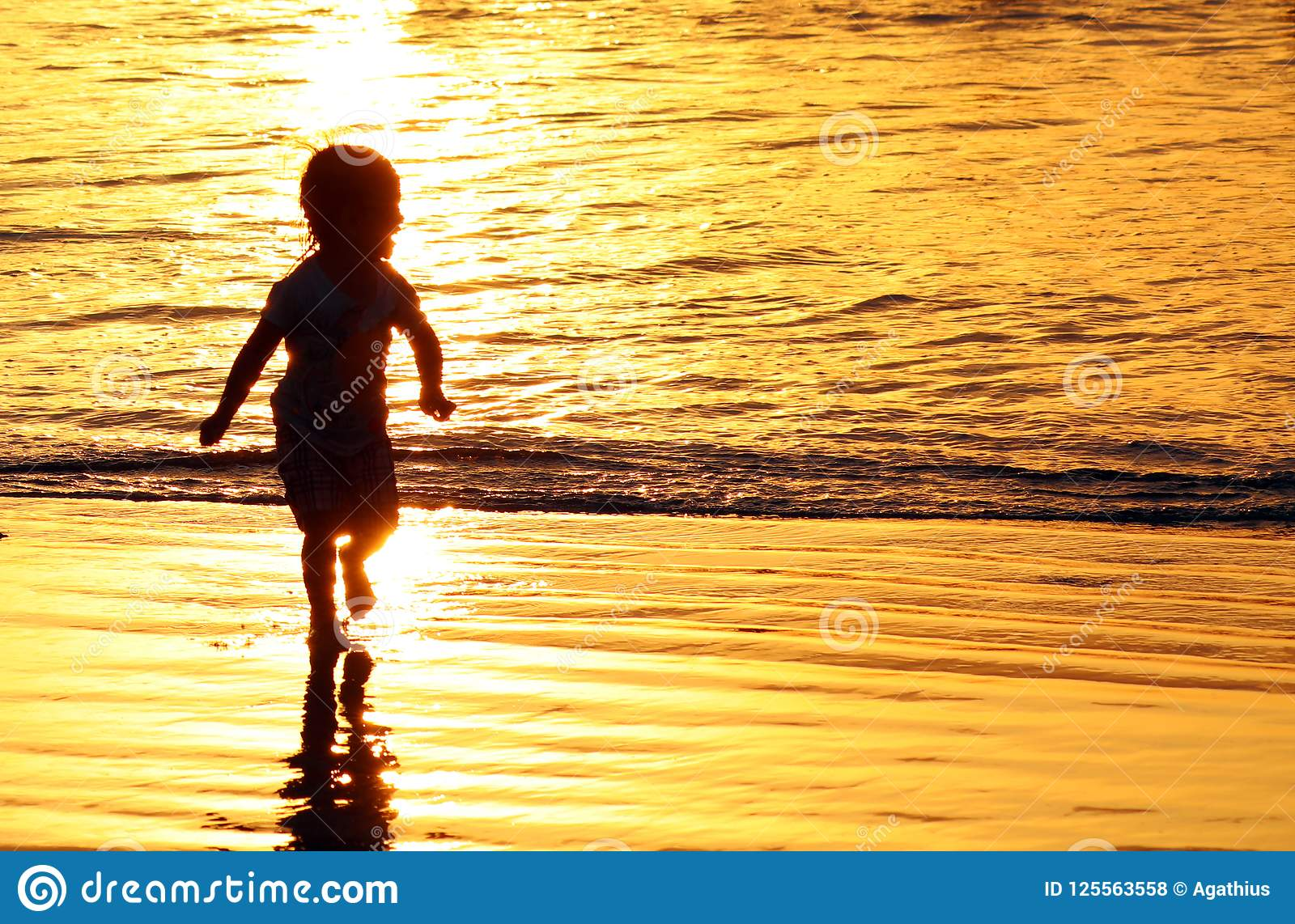 Дети играя на пляже в Бали, Индонезии во время золотого захода солнца Океан любит золото