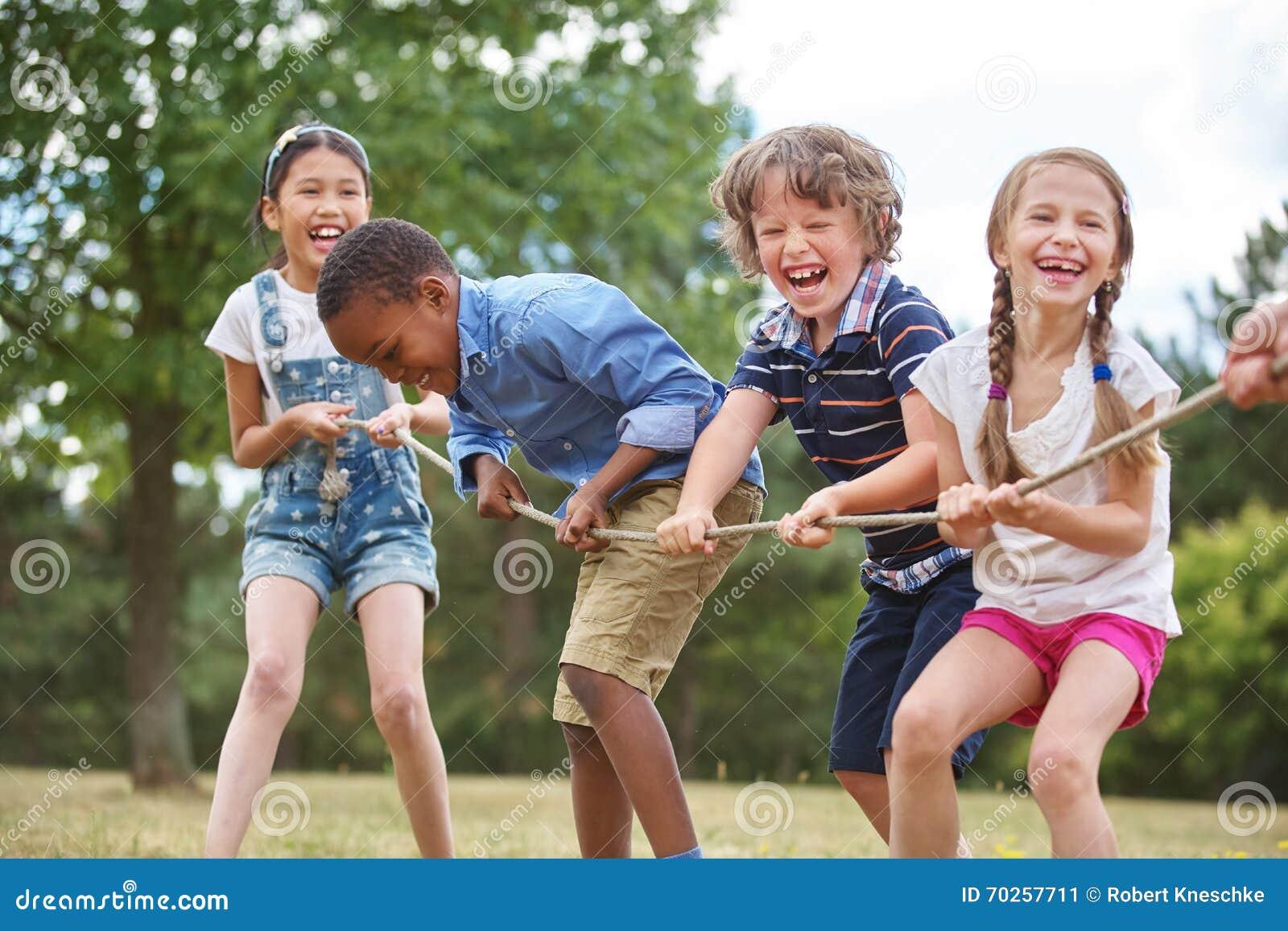 Дети играя перетягивание каната
