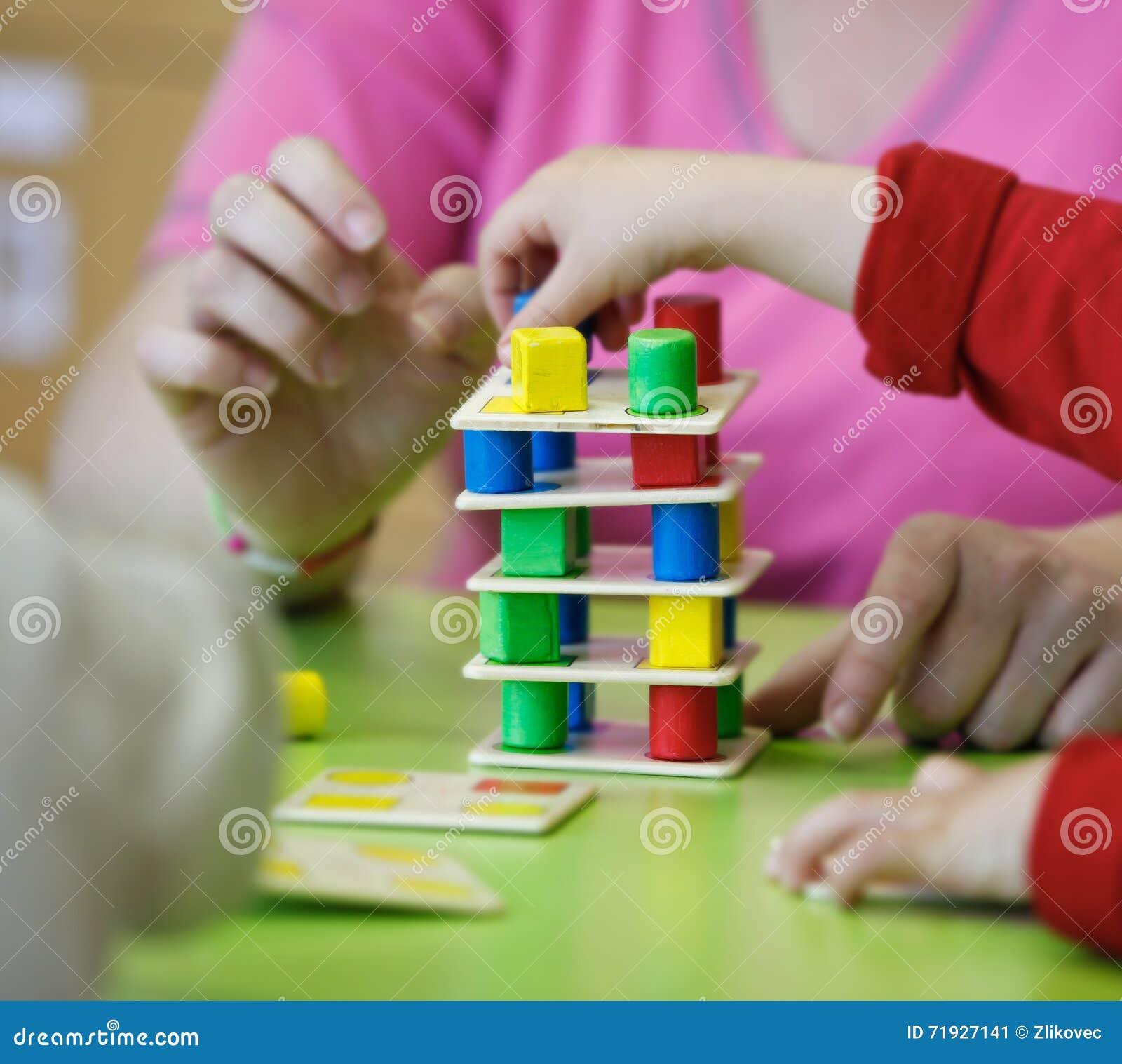 Дети играя с домодельными воспитательными игрушками