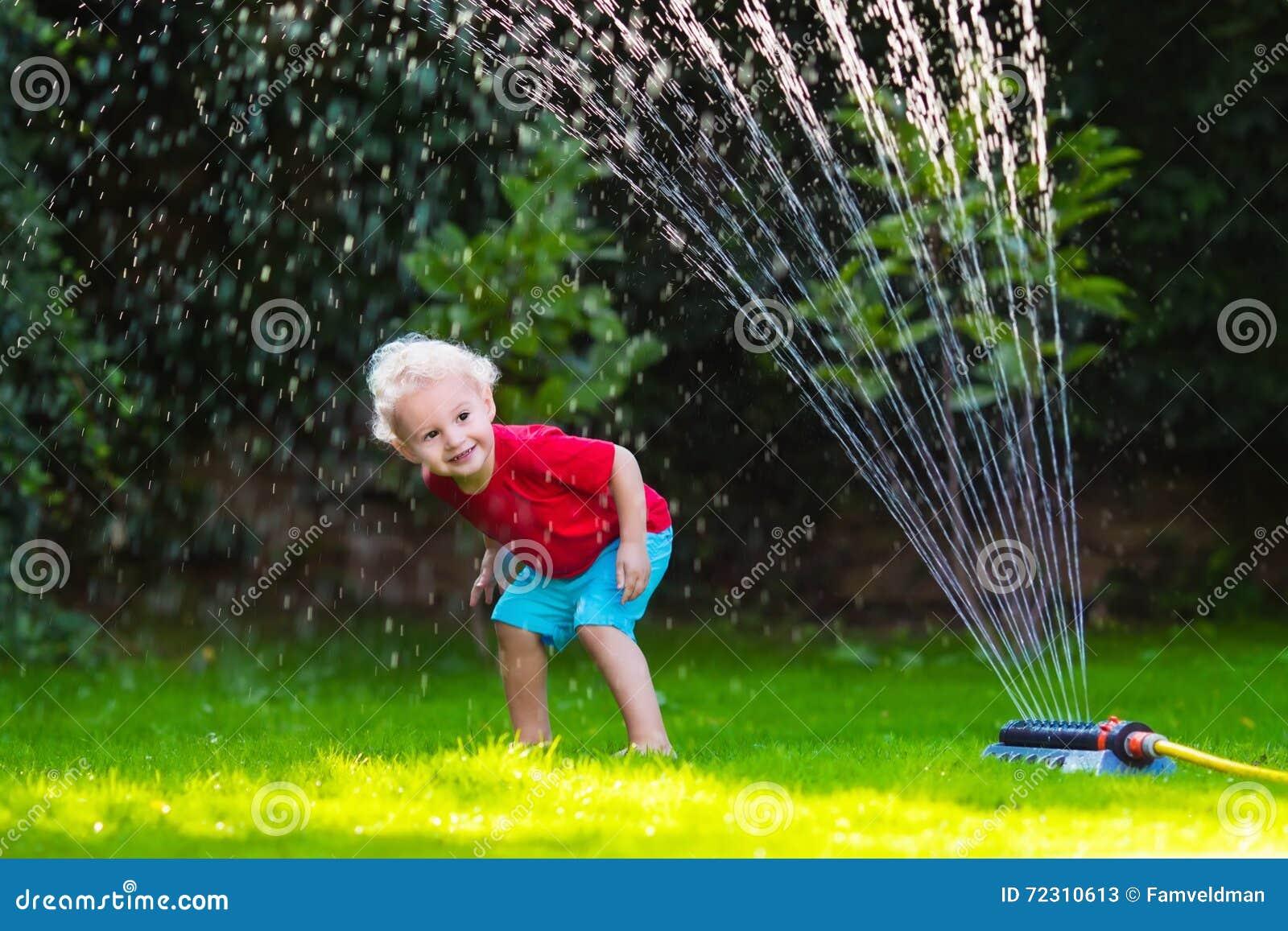 Дети играя с спринклером сада