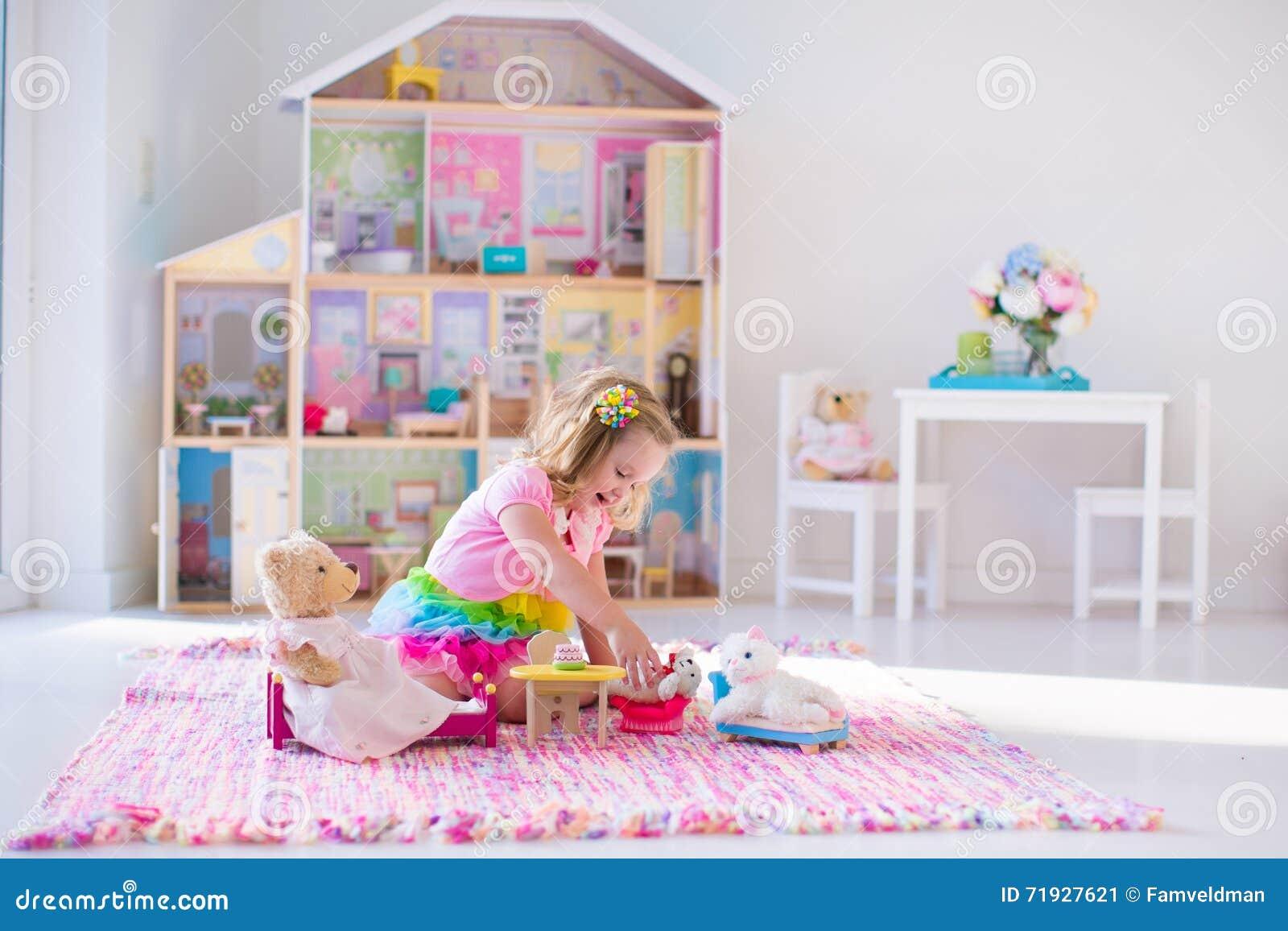 Дети играя с чучелами и кукольным домом