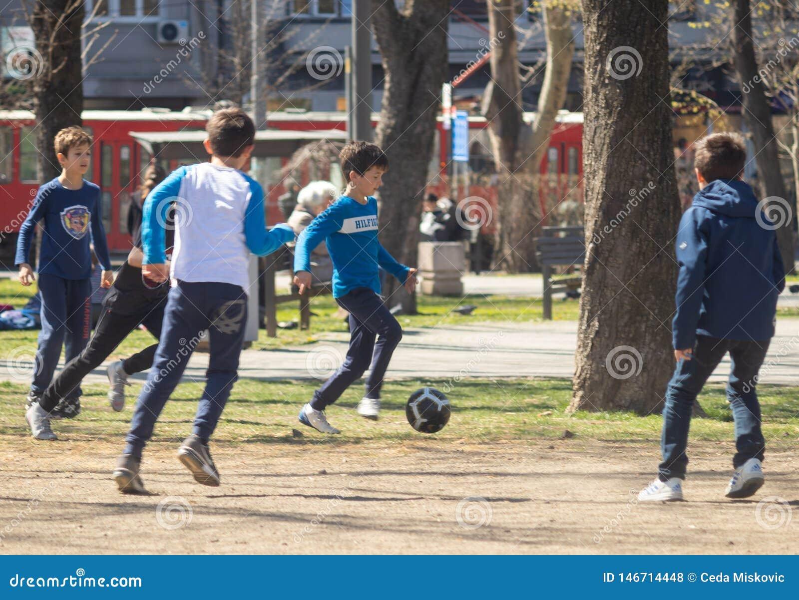 Дети играя футбол в парке на солнечный день
