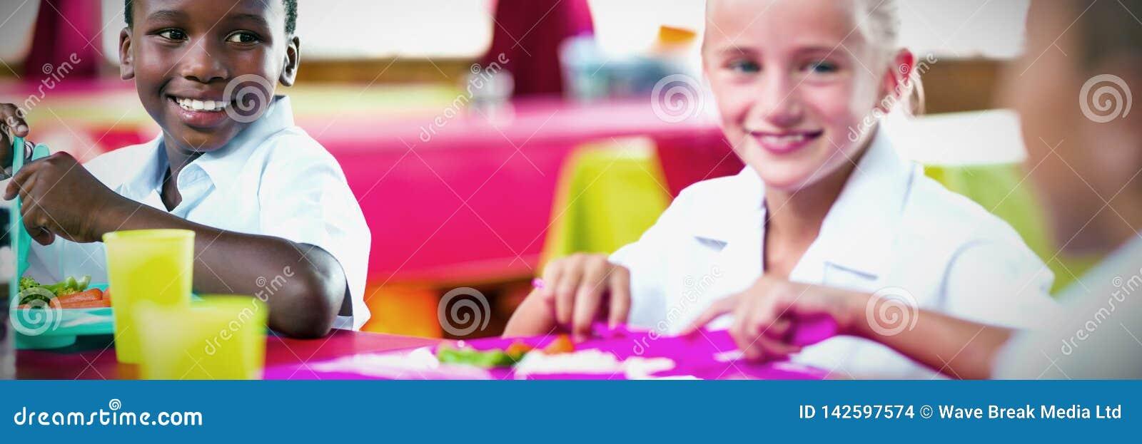 Дети имея обед во время периода отдыха в школьном кафетерии