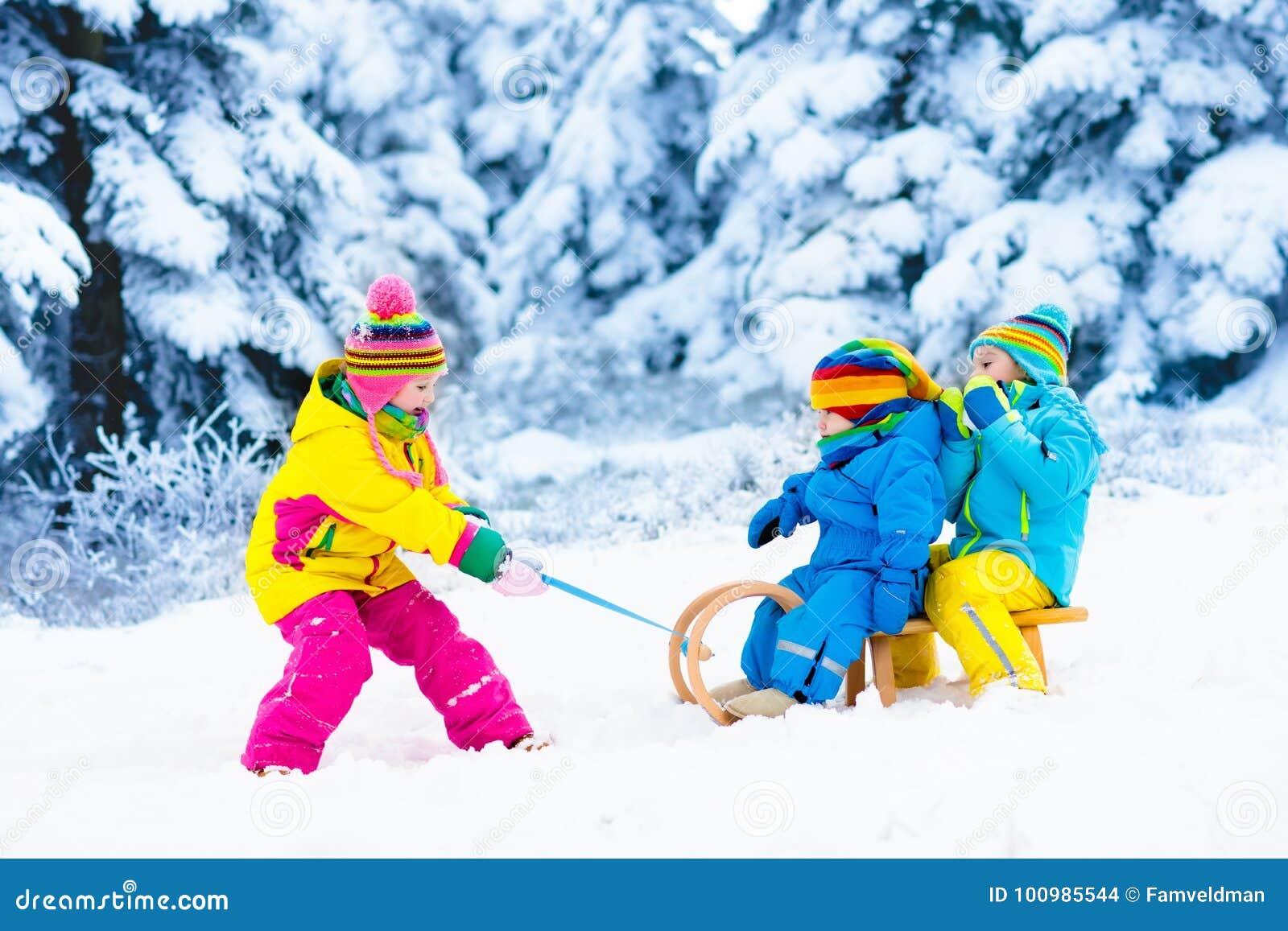 Дети на езде саней Бросаться через снег Потеха снега зимы
