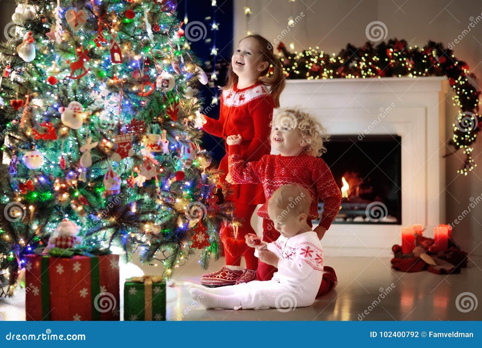 Дети на рождественской елке Дети на камине на кануне Xmas
