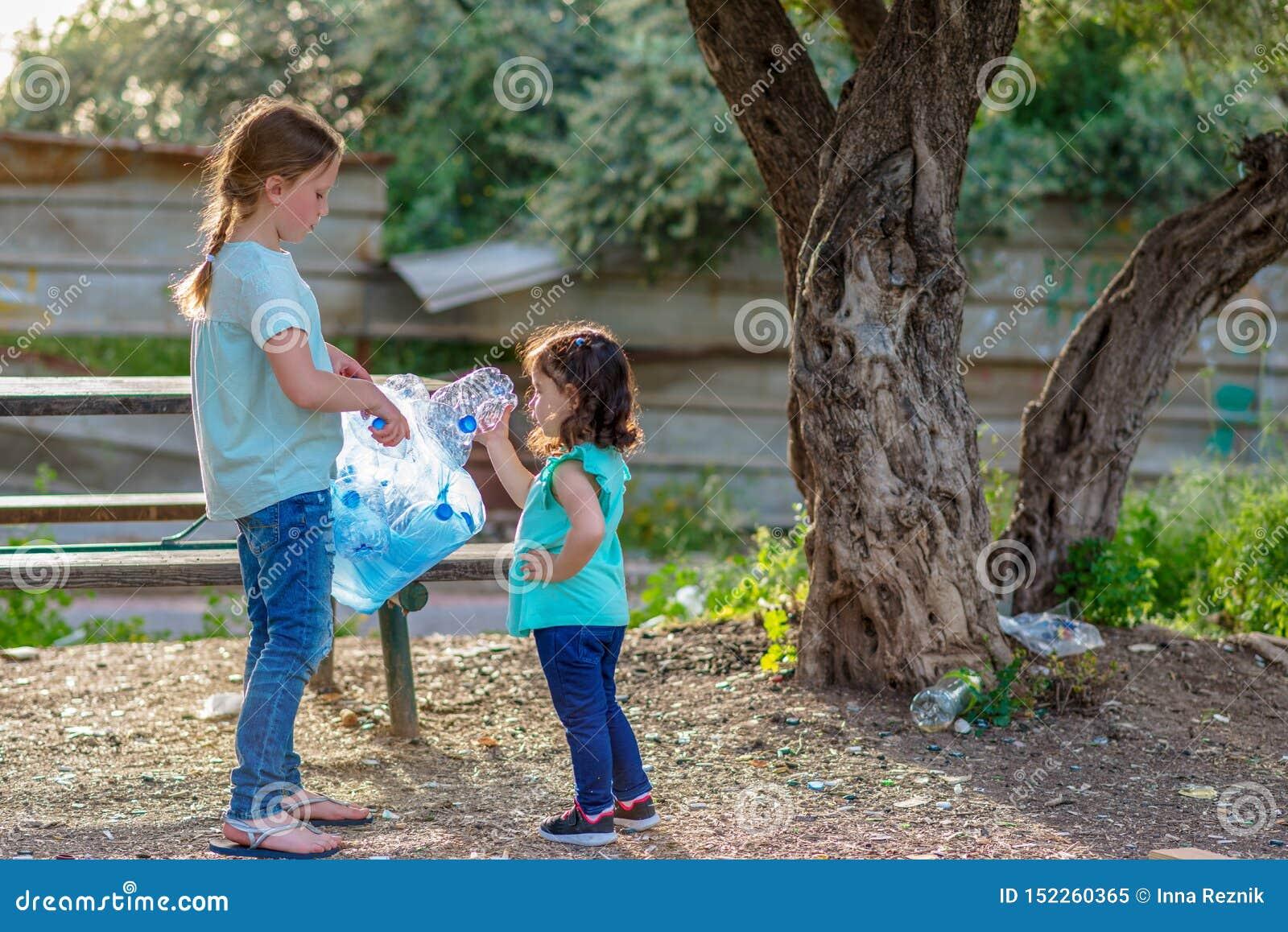 Дети очищая в парке Добровольные дети с сумкой отброса очищая вверх сор, кладя пластиковую бутылку в повторно использовать сумку