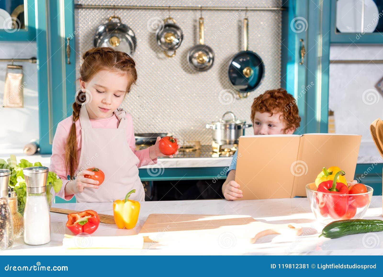 дети при поваренная книга и овощи варя совместно