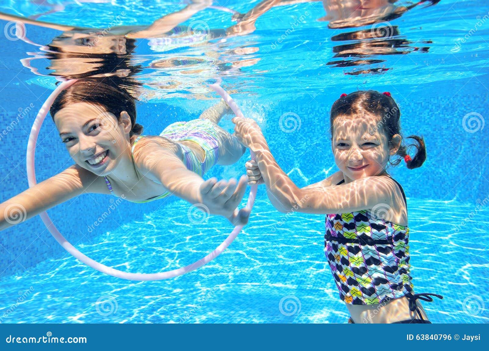 Дети плавают в бассейне подводном, счастливые активные девушки имеют потеху под водой, спорт детей