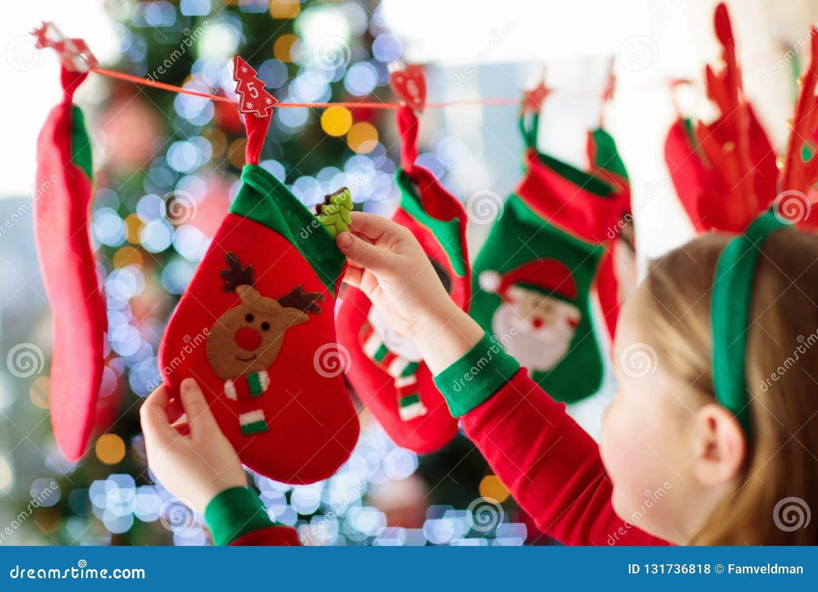 Дети раскрывая подарки на рождество Ребенок ища для конфеты и подарков в календаре пришествия на утре зимы украшенное рождество