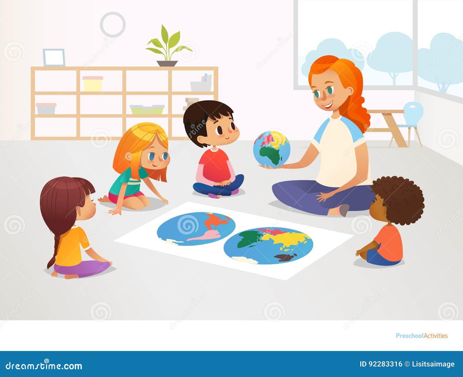 Дети сидят вокруг карты мира и учительница redhead демонстрирует их модельные земли планеты Урок землеведения