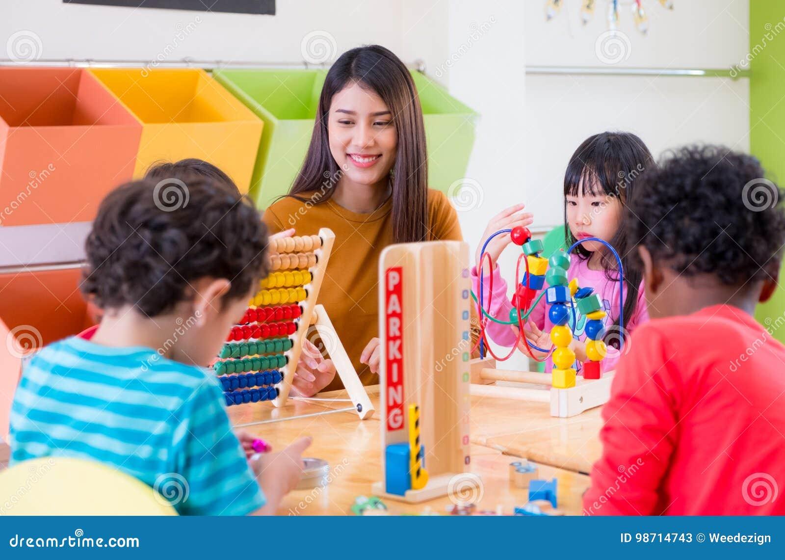 Дети смешанной гонки азиатской учительницы уча игрушка игры в classr