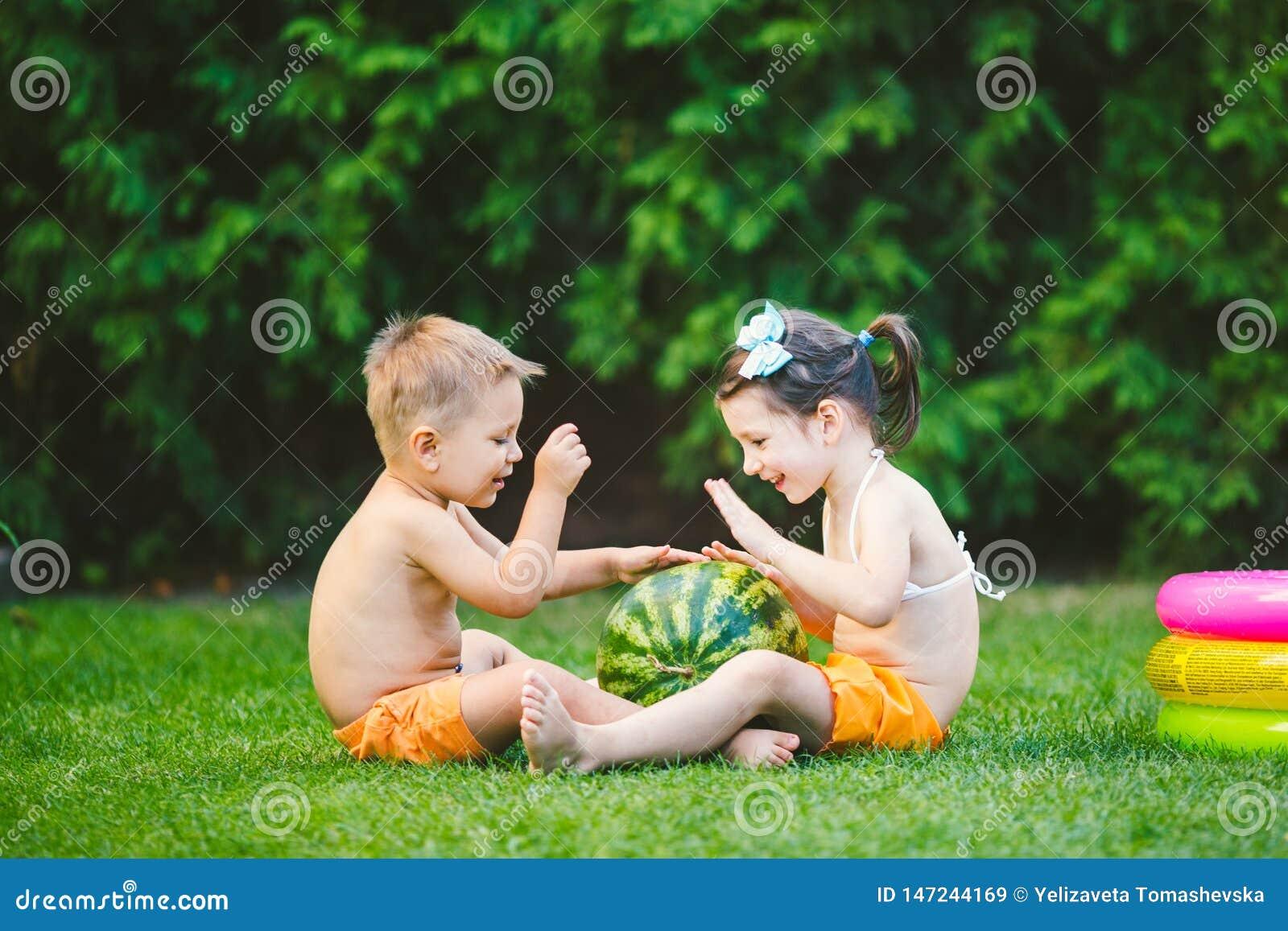 2 дет, кавказский брат и сестра, сидя на зеленой траве в задворк дома и обнимая большой вкусный сладкий арбуз