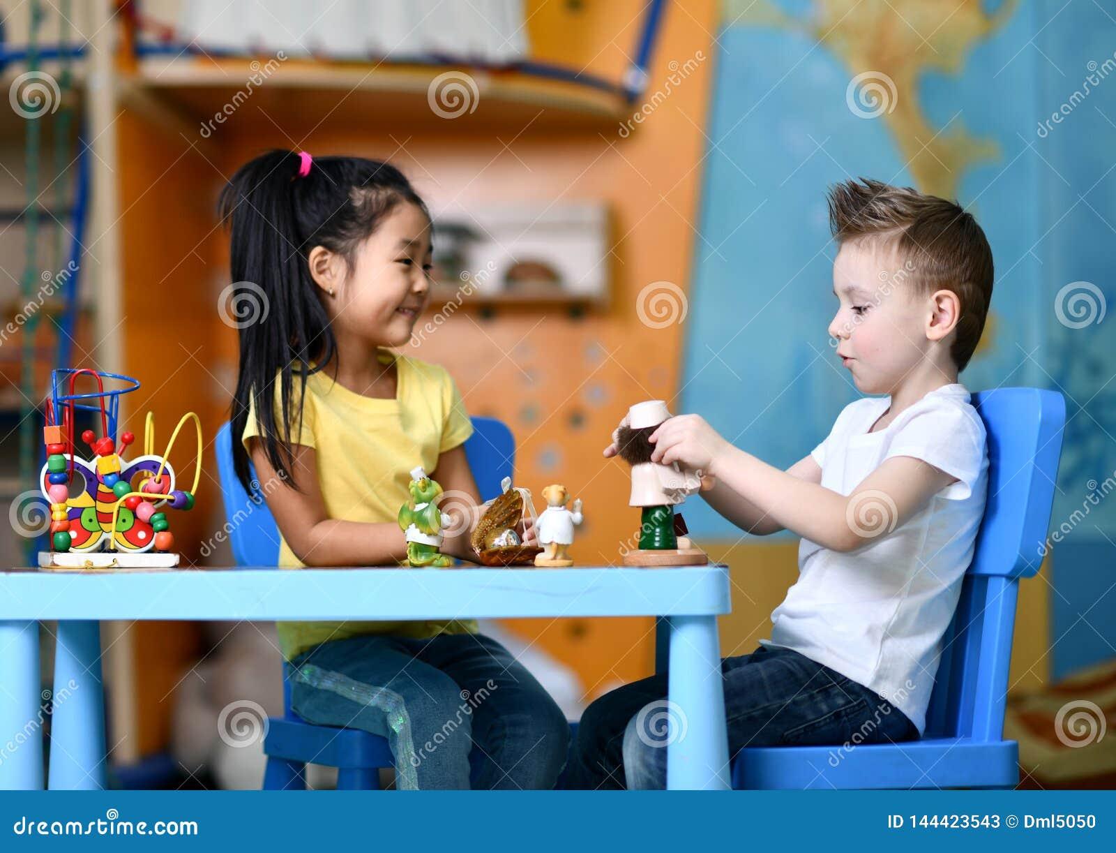 2 дет мальчик и девушка сидят на таблице и играют докторов игрушки