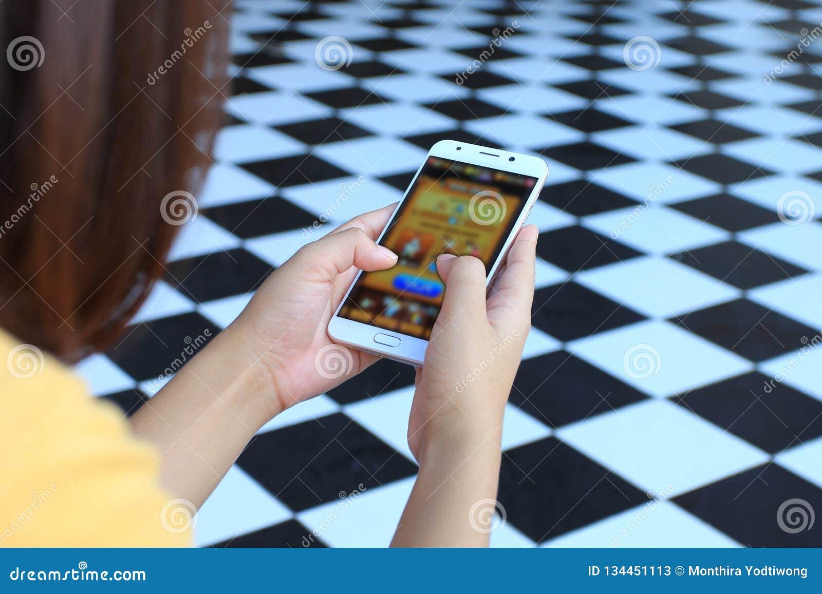 Деятельности при молодой женщины играя видеоигры на смартфоне, образовании и интернете вещей IoT