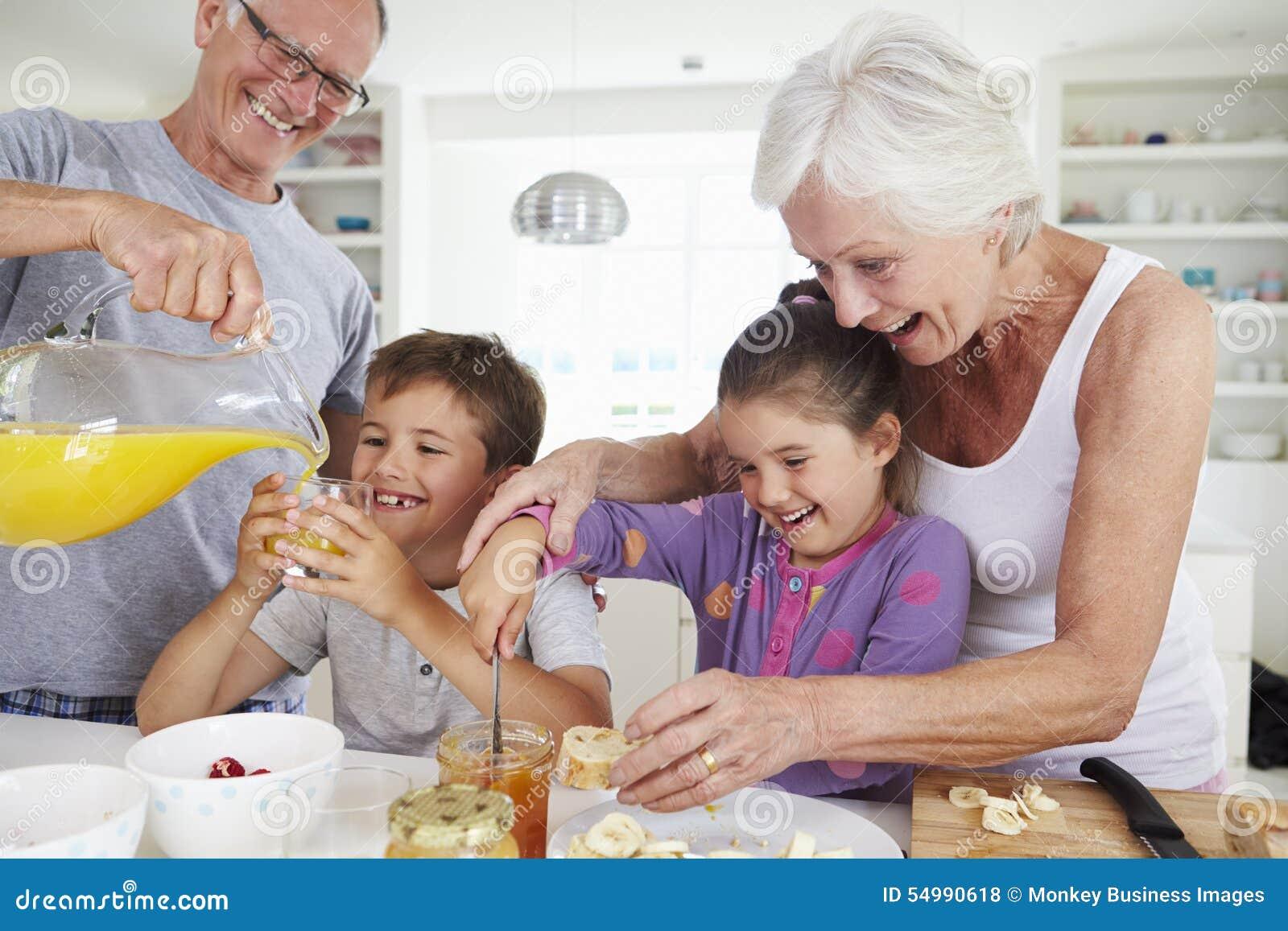 Деды при внуки делая завтрак в кухне