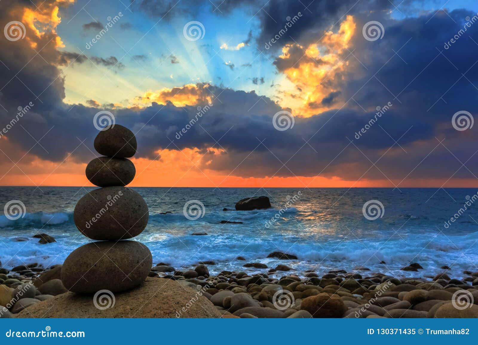 Дзэн штабелировал утесы на красивом восходе солнца