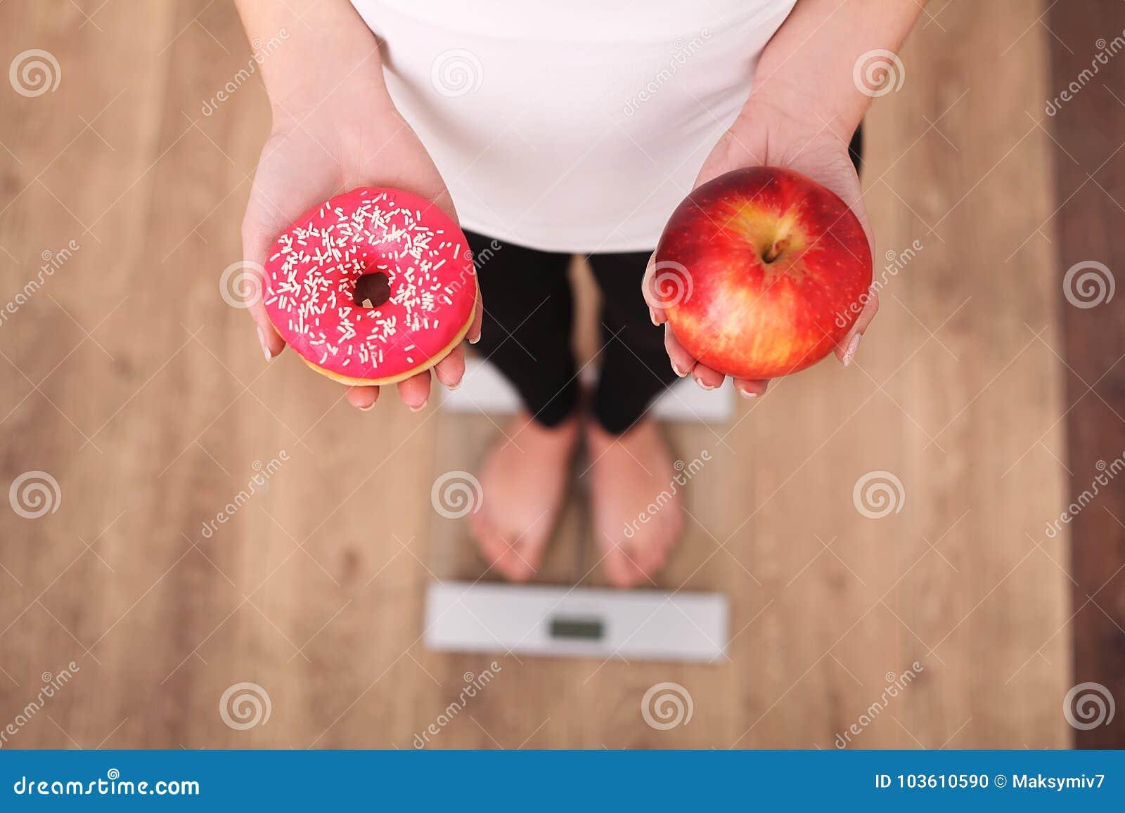 Диета Вес тела женщины измеряя на веся масштабе держа донут и яблоко Помадки нездоровая высококалорийная вредная пища Dieting, зд
