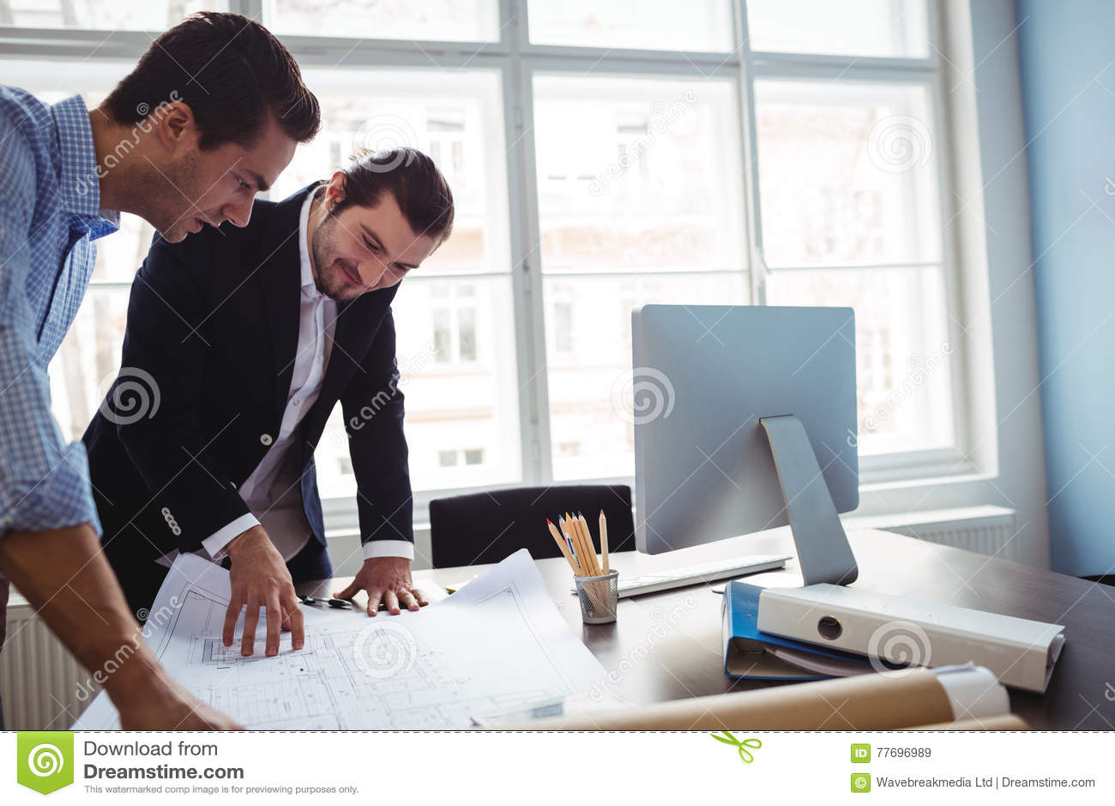 Дизайнер по интерьеру обсуждая светокопию с коллегой