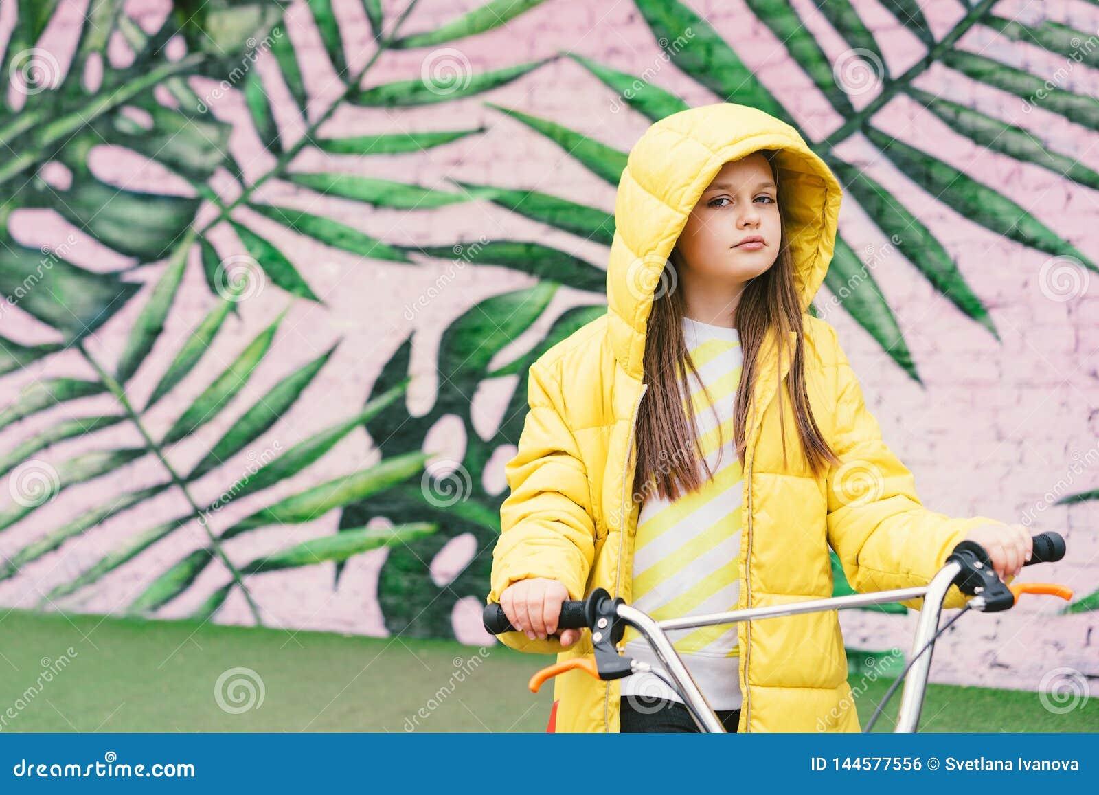 Длинн-с волосами белокурая девушка в желтом свитере и желтой куртке