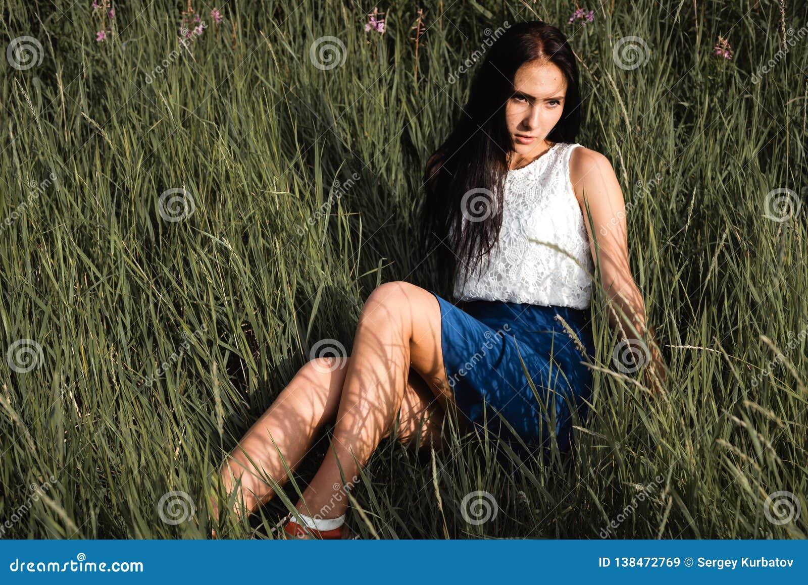 Длинн-с волосами предназначенная для подростков девушка сидит на луге травы