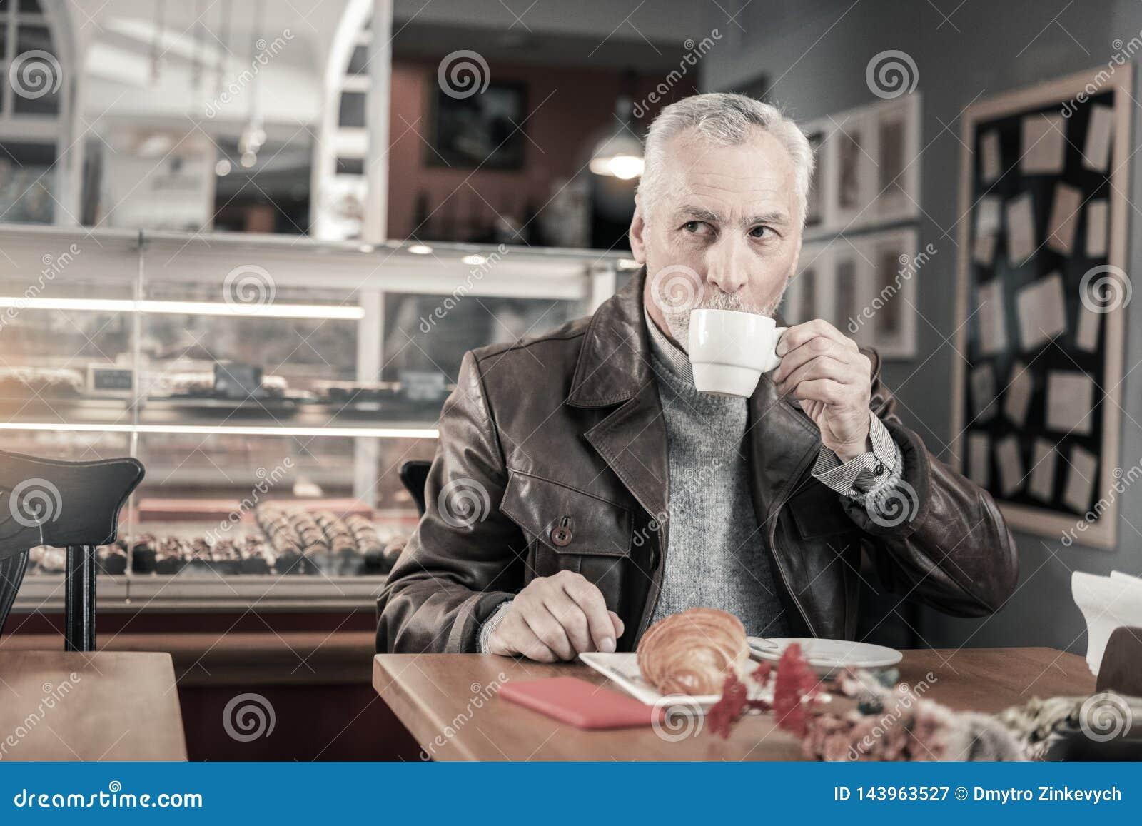 Добросердечный зрелый человек выпивая вкусный кофе во время перерыва