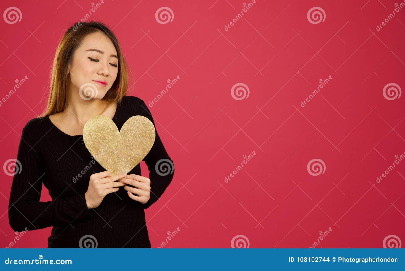 Довольно молодая азиатская женщина в студии держа сердце золота к ей