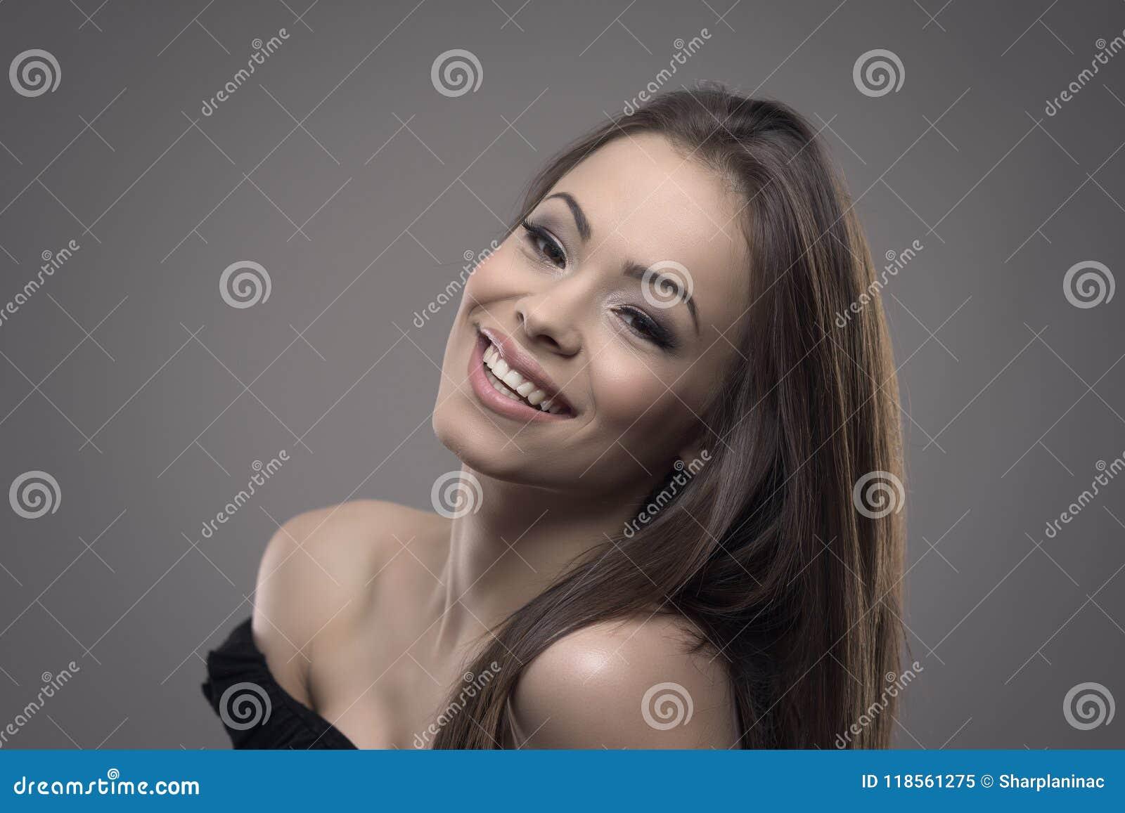 Довольно молодая жизнерадостная женщина с совершенной улыбкой усмехаясь и смотря камеру при голова озаглавленная назад