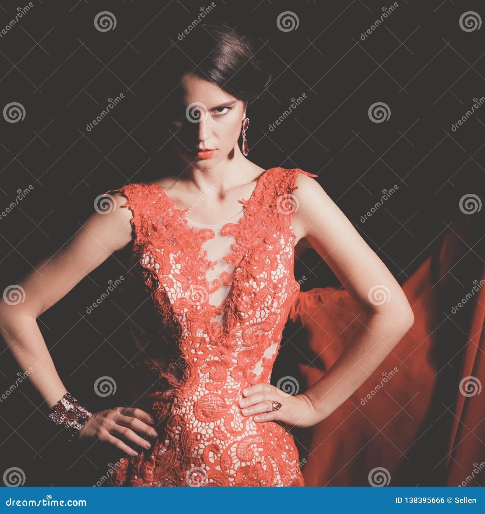 Довольно молодая модельная женщина с темными волосами в изумительном длинном красном платье