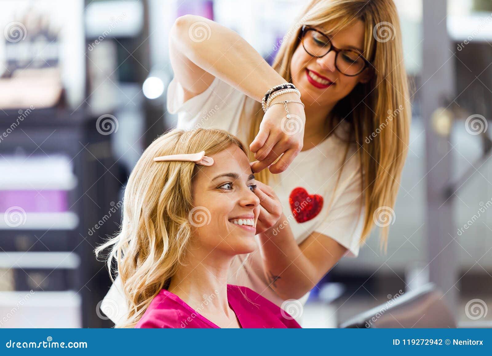 Довольно молодой парикмахер делая стиль причёсок к милой женщине в салоне красоты