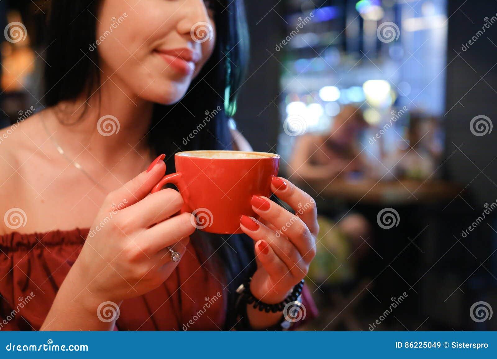 Довольно молодая женская женщина держит в чашке руки и выпивает кофе ag