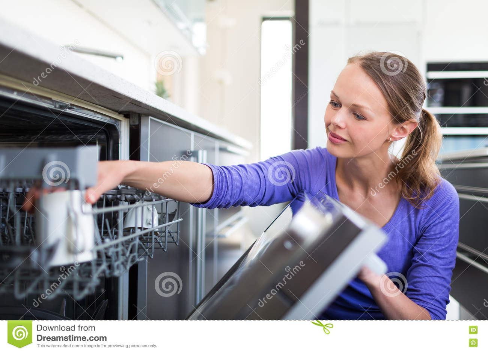 Довольно, молодая женщина в ее современной и хорошо оборудованной кухне