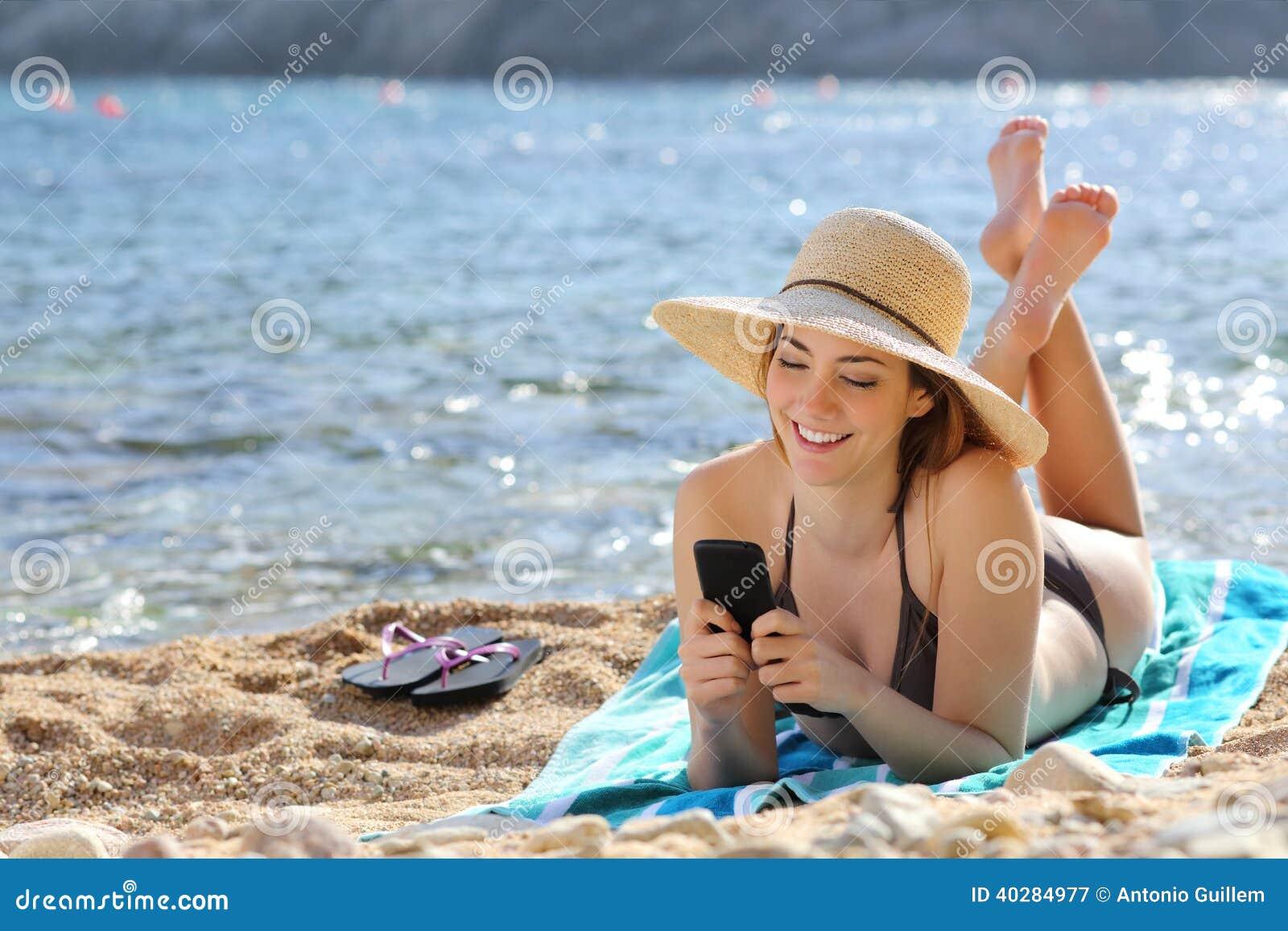 Довольно счастливая женщина читая умный телефон на пляже