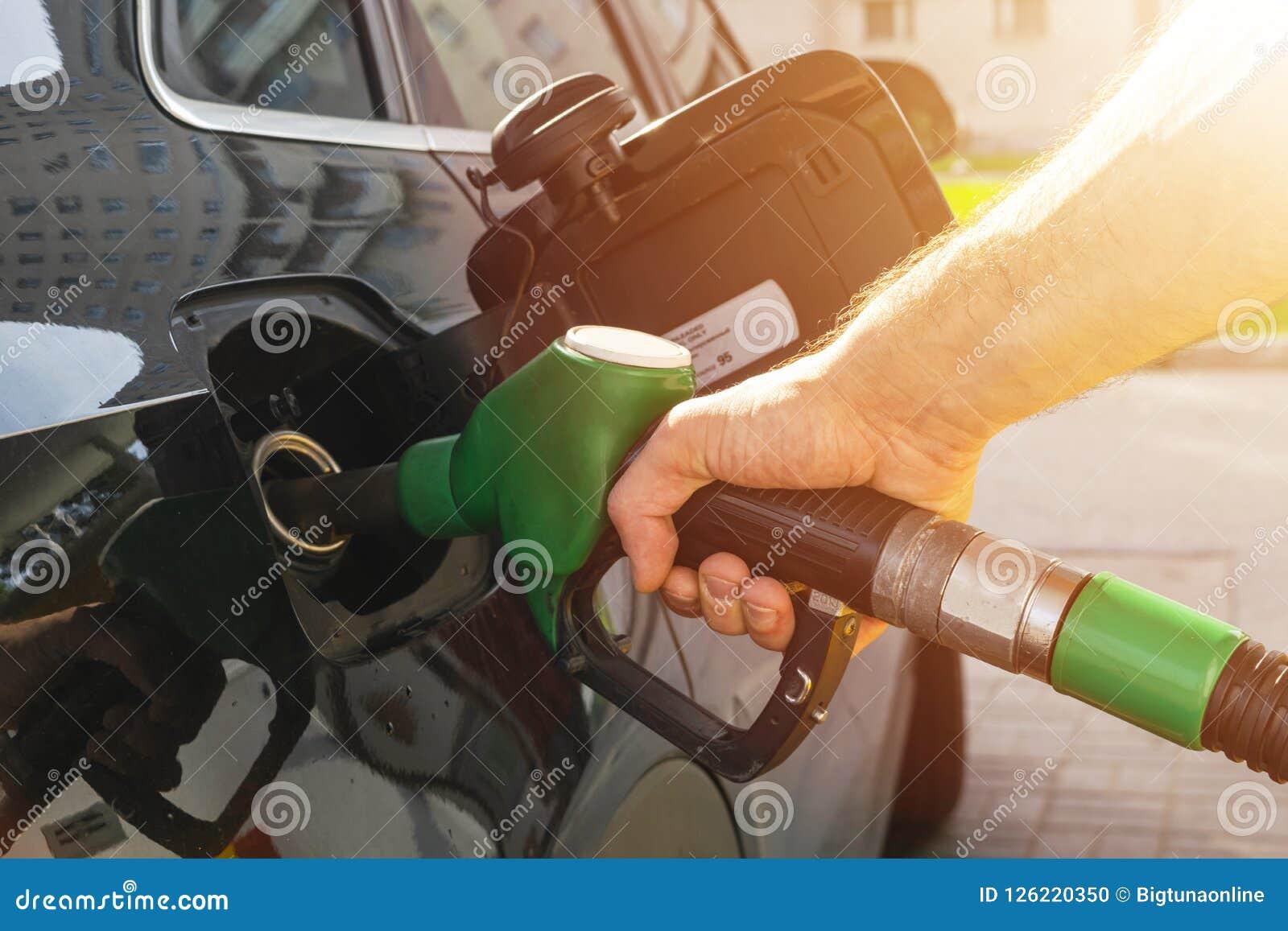 Дозаправлять автомобиль на насосе для подачи топлива бензоколонки Бензин руки водителя человека refilling и нагнетая смазывает ав