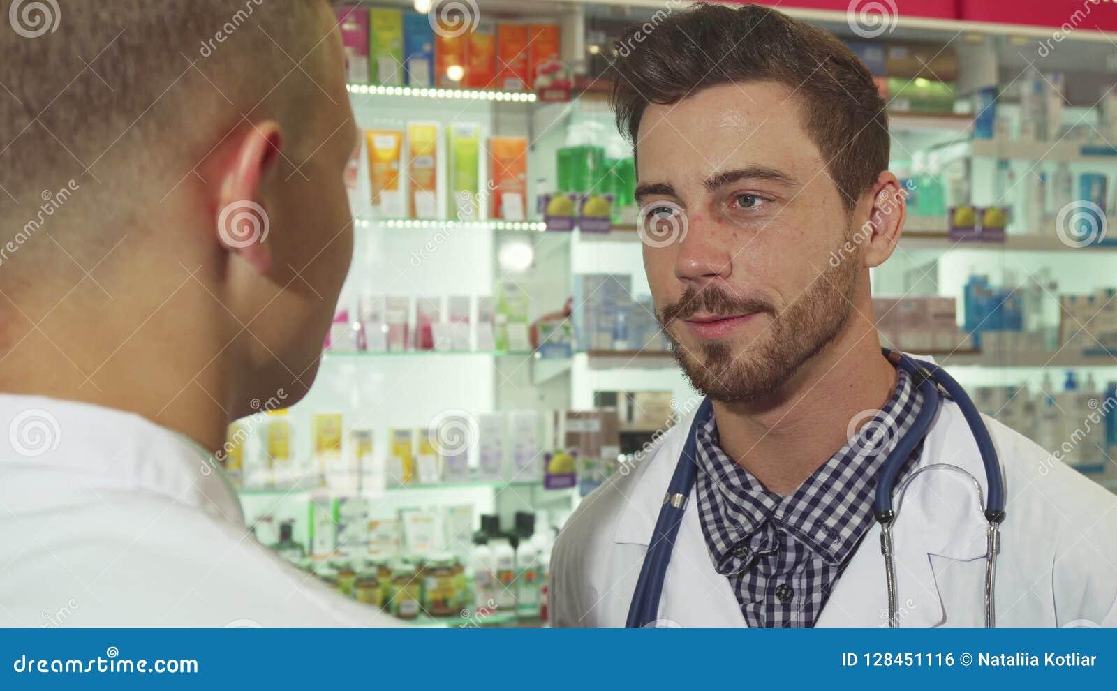 Доктор говоря к пациенту на аптеке