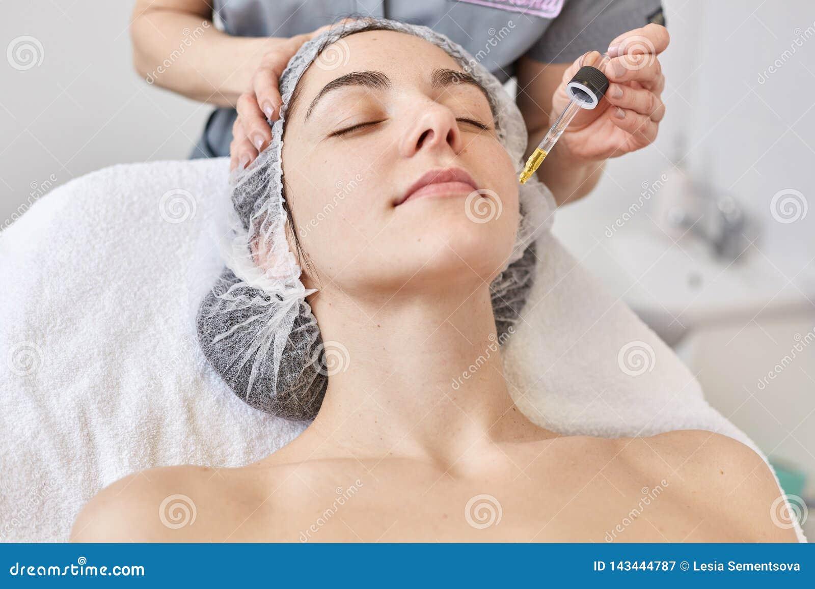 Доктор делает процедуру по beautician, сыворотку витамина applys для того чтобы смотреть на красивой женщины, клиента клиники кос