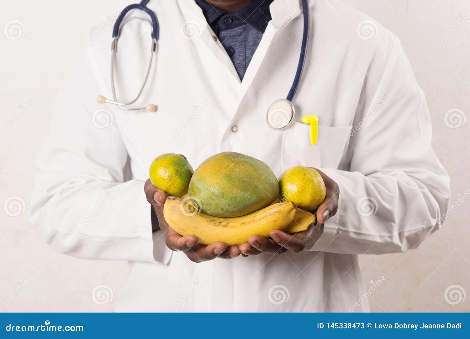 Доктор держа и представляя плоды в руках
