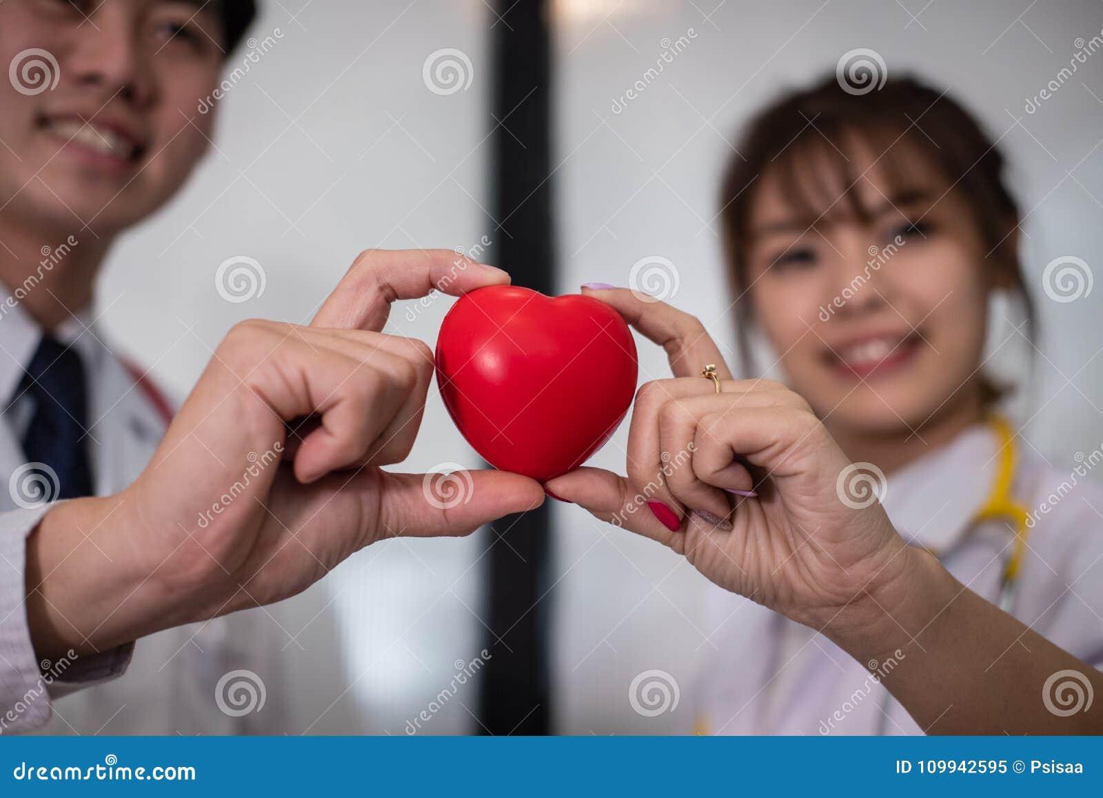 Доктор держа красное сердце на больнице медицинский, здравоохранение, cardi