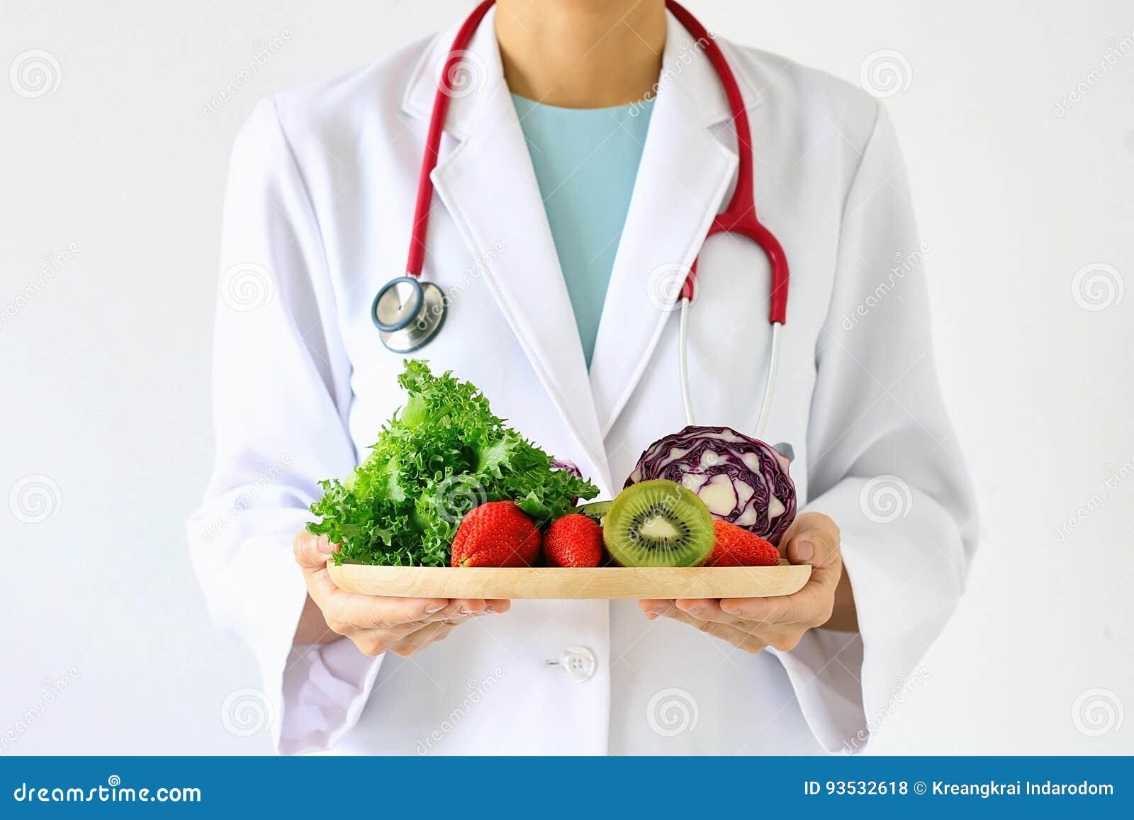 Доктор держа свежий фрукт и овощ, здоровое питание