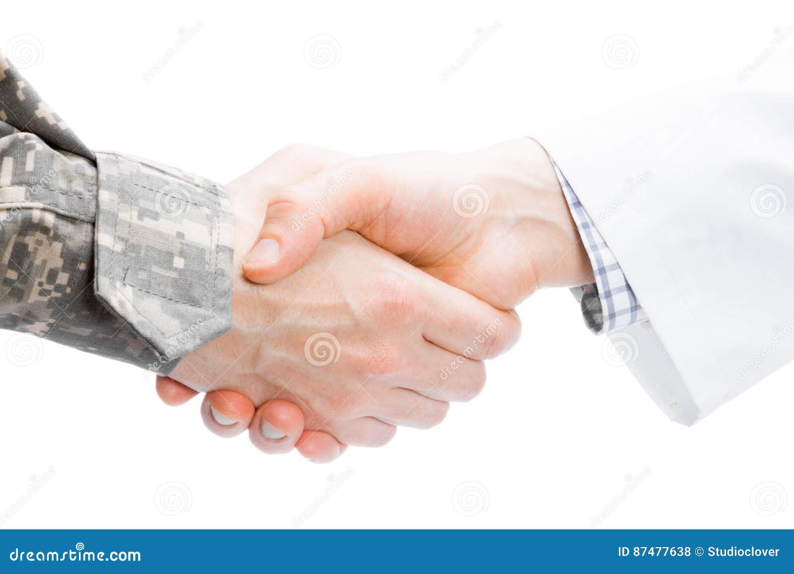 Доктор и военный тряся руки на белой предпосылке - близкой поднимающей вверх съемке студии