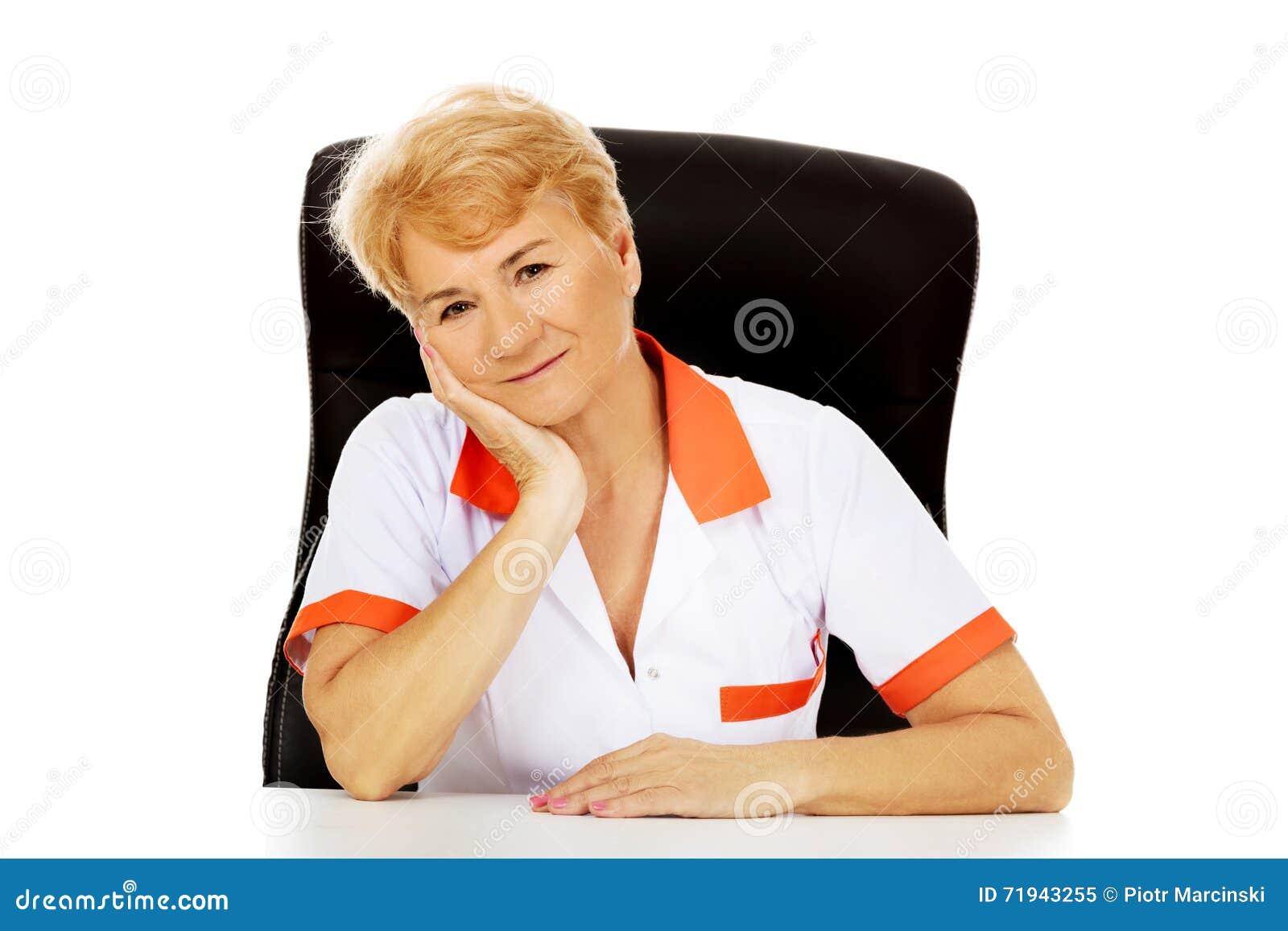 Доктор или медсестра улыбки пожилые женские сидя за столом полагаясь в наличии