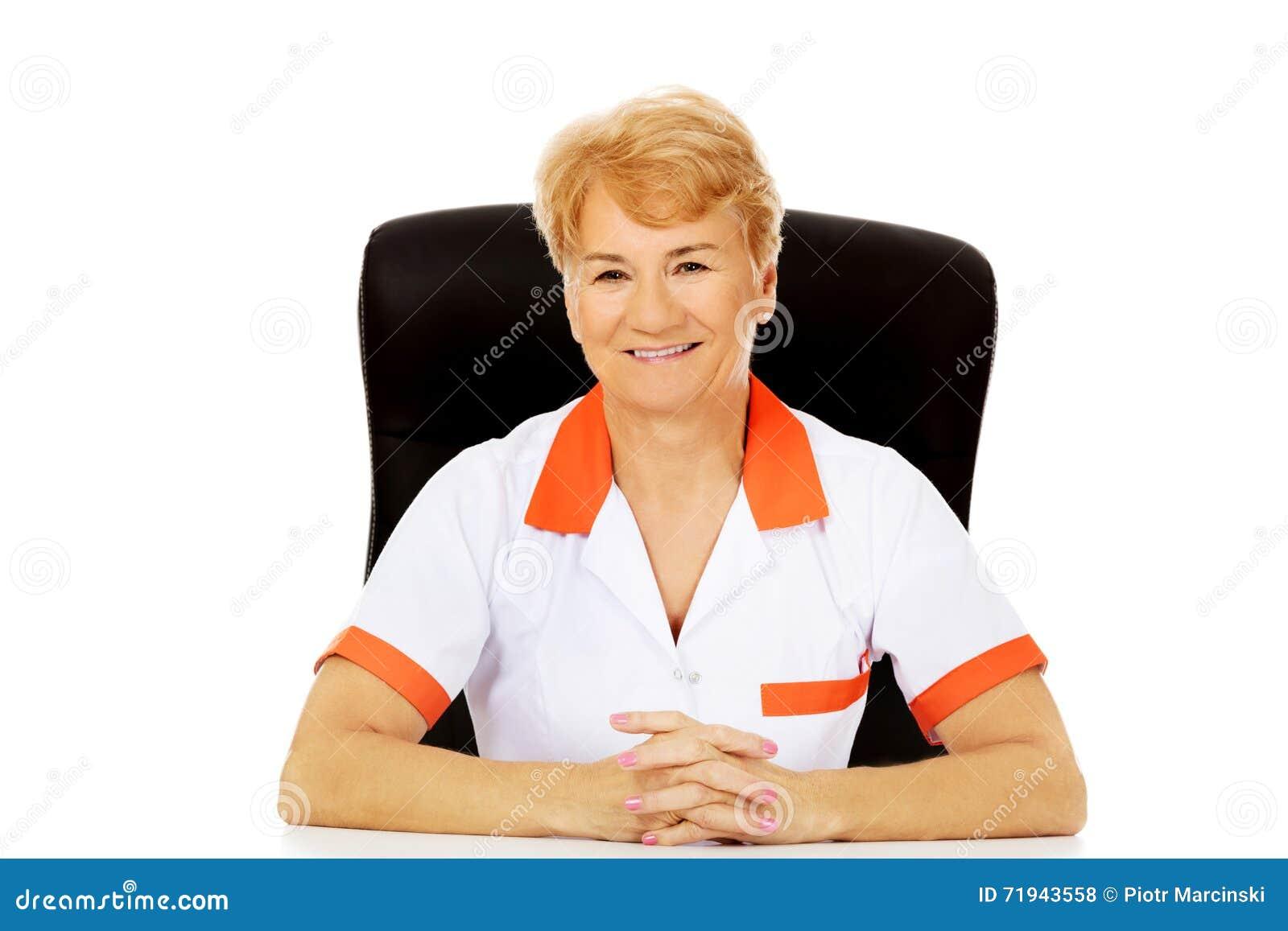 Доктор или медсестра улыбки пожилые женские сидя за столом
