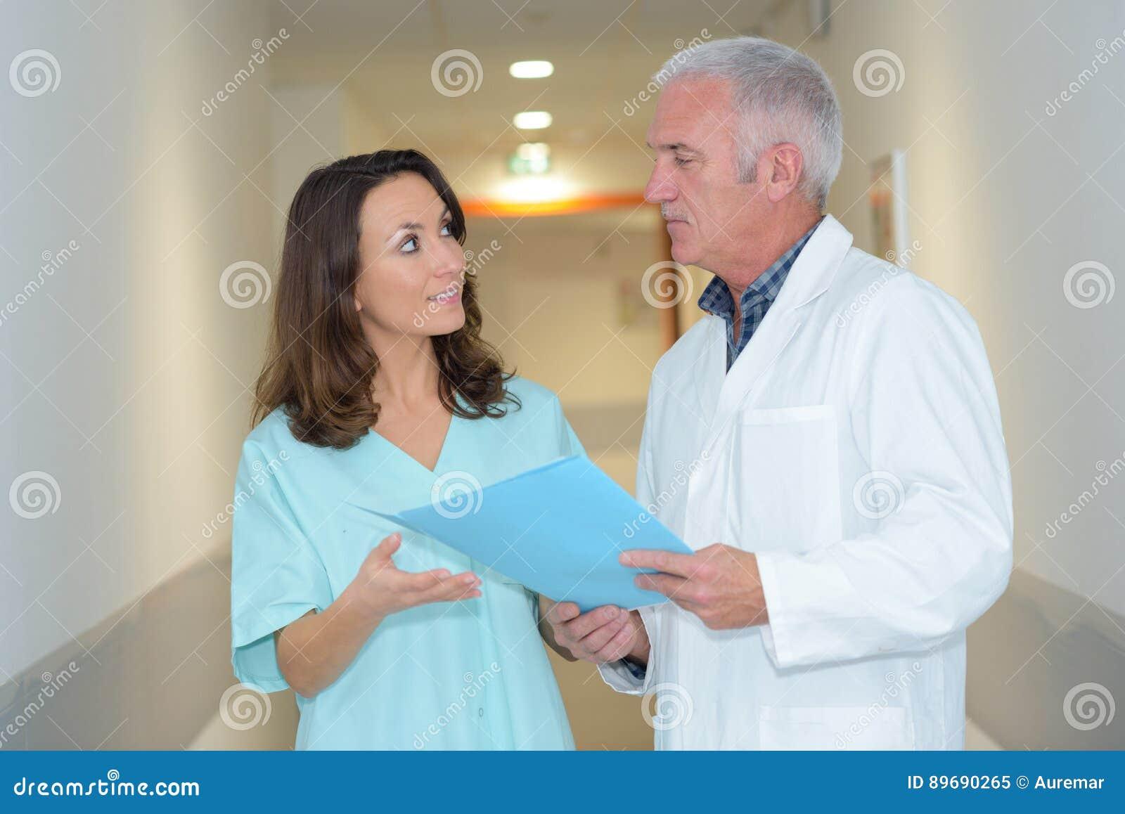 Доктор и помощник врача имея переговор