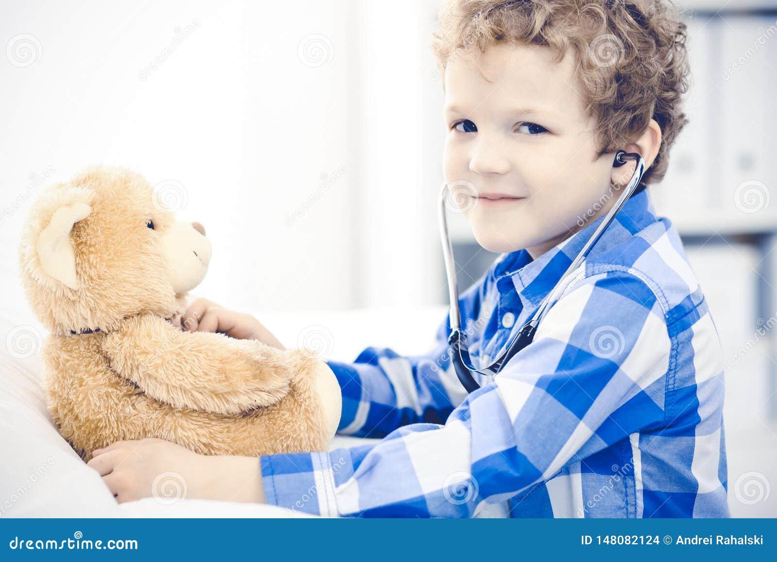 Доктор и терпеливый ребенок Мальчик врача рассматривая Регулярное медицинское посещение в клинике Медицина и здравоохранение