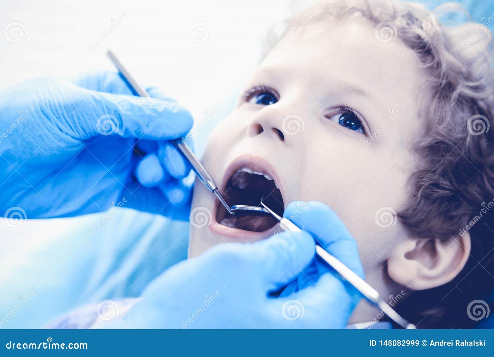 Доктор и терпеливый ребенок Мальчик имея его зубы быть расмотренным с медициной дантиста, здравоохранением и концепцией стоматоло