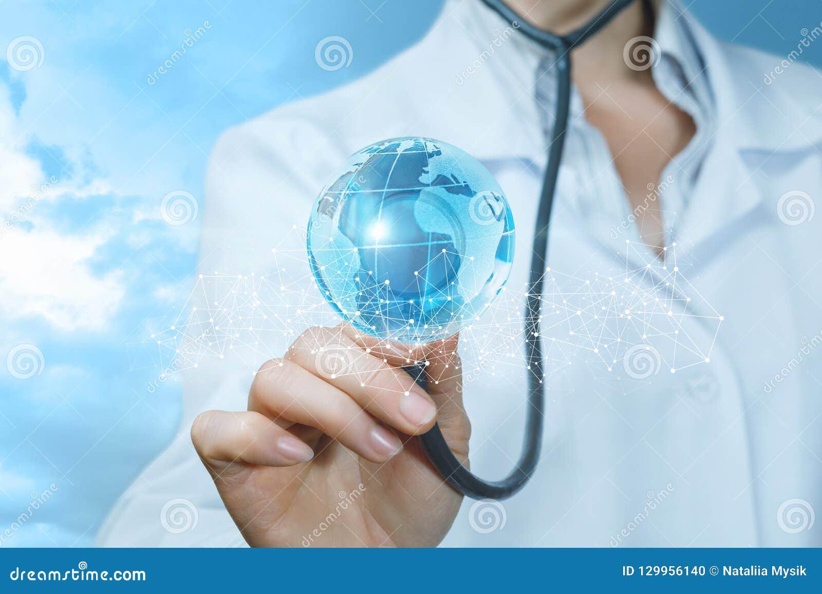 Доктор касается яркой глобальной карте за загородкой беспроводных связей с ее стетоскопом