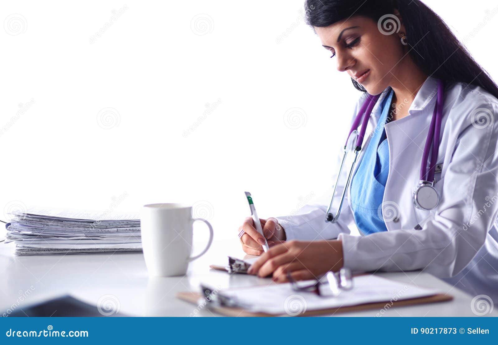 Доктор красивых детенышей усмехаясь женский сидя на столе