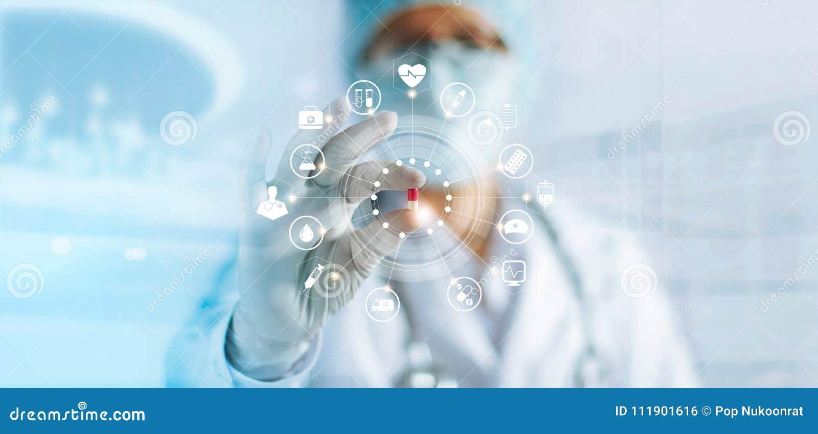 Доктор медицины держа пилюльку капсулы цвета в руке с сетевым подключением значка медицинским на современном интерфейсе виртуальн