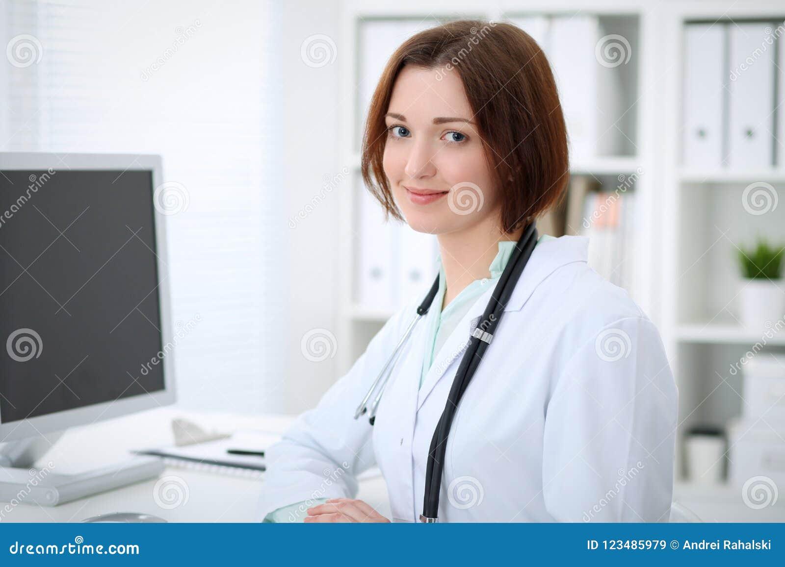 Доктор молодого брюнет женский сидя на таблице и работая с компьютером на офисе больницы